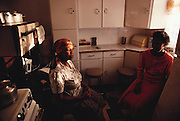 Leah and Anna, Poppy Qampie's mother and sister, respectively, visit in the kitchen of Poppy's house in Soweto, South Africa. Published in Material World page 27. The Qampie family lives in a 400 square foot concrete block duplex house in the sprawling area of Southwest Township (called Soweto), outside Johannesburg (Joberg) South Africa.