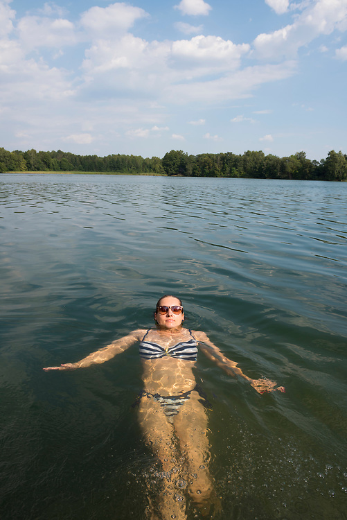 Trakai, Lithuania - August 8, 2015: A young woman, Aistė, enjoys a summer swim in Lake Luka in Trakai, Lithuania. The town, best known for its picturesque red-brick castle, is located 28 kilometers from Vilnius.