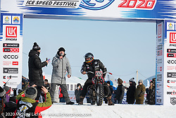 """Victor Dokuchaev on his 1942 WR 45"""" Harley-Davidson Flathead racer getting introduced to the crowd from the stage during the opening ceremonies of the Baikal Mile Ice Speed Festival opening ceremonies where participants on the big stage were introduced to the crowd one at a time. Maksimiha, Siberia, Russia. Saturday, February 29, 2020. Photography ©2020 Michael Lichter."""