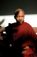 Burma/Myanmar, Mandalay. Portrait of a novice monk sitting on a bench.