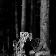 Nude African American woman crouching by a tree stump wrapping her arms around herself. Black and white. Nature Deficit Disorder I, MR
