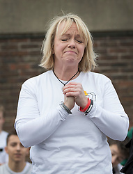 © Licensed to London News Pictures. 04/03/2017. Guildford, UK. Deborah Newman closes her eyes during a minutes silence at a memorial with hundreds of free runners gathered to remember her son Nye Newman who died in January. Nye Newman, whose death is thought not to be related to Parkour, died in Paris. Free running or Parkour involves jumping and climbing on building, railings and walls.  Photo credit: Peter Macdiarmid/LNP