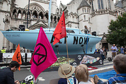 Extinction Rebellion blue boat Polly Higgins during disruption across 5 UK cities calling on Government to ACT NOW outside the Royal Courts of Justice after it was announced last week that more than 1,000 activists who participated in previous demonstrations were facing prosecution, on 15th July 2019 in London, England, United Kingdom. Extinction Rebellion is a climate change group started in 2018 and has gained a huge following of people committed to peaceful protests. These protests are highlighting that the government is not doing enough to avoid catastrophic climate change and to demand the government take radical action to save the planet.