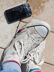 Person's leg with torn canvas shoes and cracked smartphone, Bavaria, Germany
