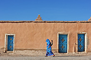 Traditional dressed woman walks with her child in front of an old clay house, Boumalne du Dades, Morocco.