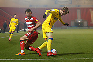 Joe Pigott of AFC Wimbledon goes past Doncaster defender Andrew Butler  during the EFL Sky Bet League 1 match between Doncaster Rovers and AFC Wimbledon at the Keepmoat Stadium, Doncaster, England on 26 January 2021.