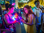 31 DECEMBER 2014 - BANGKOK, THAILAND:  A woman buys a hat with flashing lights at the New Year's party in Rathaprasong. Hundreds of thousands of people pack into the Ratchaprasong Intersection in Bangkok for the city's annual New Year's Eve countdown. Many Thais go the Erawan Shrine and Wat Pathum Wanaram near the intersection to pray and make merit before going to their New Year's parties.   PHOTO BY JACK KURTZ