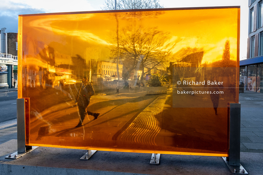 Seen through an orange-coloured prism, a figure walks along a south London street, its distorted perspective and geometry caused by the convex and concave shape of its thick lens, on 29th January 2021, in London, England.