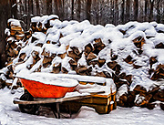 Snow covered firewood stacked for fuel for a sugar shack making maple syrup.