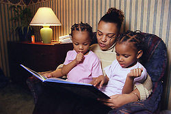 Mother reading a book with twin girls,