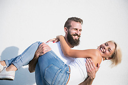 Happy young man carrying woman in front of wall, Bavaria, Germany