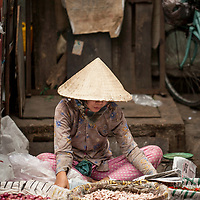 A vendor reads a newspaper while waiting for customers at the Phú Nhuận vegetable market in Ho Chi Minh City, also known as Saigon, Vietnam.