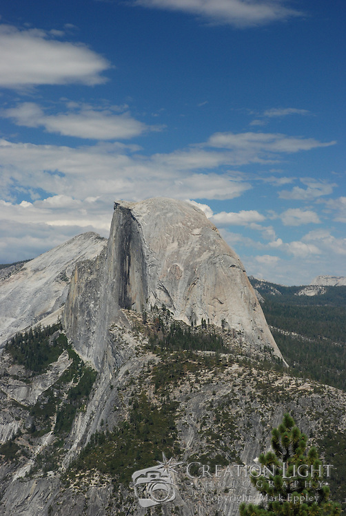 Yosemite National Park's most well-know feature is Half Dome, which stands at an altitude of 8,836 feet and 4,737 feet above the valley floor. As the rock was exposed, weathering and exfoliation of shell-like outer layers of the rock shaped the dome portion of the rock to its current shape. The summit is attainable as a day hike in the summer, if you have the stamina to undertake a 17-mile roundtrip hike with 5000 feet of elevation gain from the valley floor.