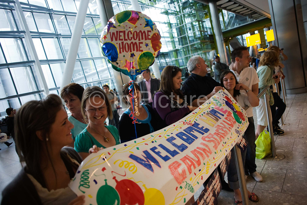 """A helium-filled Welcome Home balloon floats in the air and a home-made banner stretches across Heathrow Airport's Terminal 5 arrivals hall. Three families have gathered to meet their respective sons who have been travelling around the world during their university gap year sabbatical trip of a lifetime. With balloon and banner amid the hectic concourse where other relatives greet their loved-ones after months away from home on their adventures. This is a tradition practised across the world's airports where families are separated by the need to travel or work in other countries and the emotion of meeting again after long absences is always hard. From writer Alain de Botton's book project """"A Week at the Airport: A Heathrow Diary"""" (2009)."""