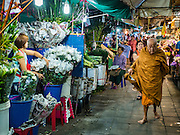 24 FEBRUARY 2016 - BANGKOK, THAILAND: A Buddhist monk walks past sidewalk vendors in front of Pak Khlong Talat in Bangkok. Bangkok government officials announced this week that vendors in Pak Khlong Talat, Bangkok's well known flower market, don't have to move out on February 28. City officials are trying to clear Bangkok's congested sidewalks and they've cracked down on sidewalk vendors. Several popular sidewalk markets have been closed in recent months and the sidewalk vendors at the flower market had been told they would be evicted at the end of the month but after meeting with vendors and other stake holders city officials relented and said vendors could remain but under stricter guidelines regarding sales hours. The flower market is one of the best known markets in Bangkok and has become a popular tourist destination.        PHOTO BY JACK KURTZ