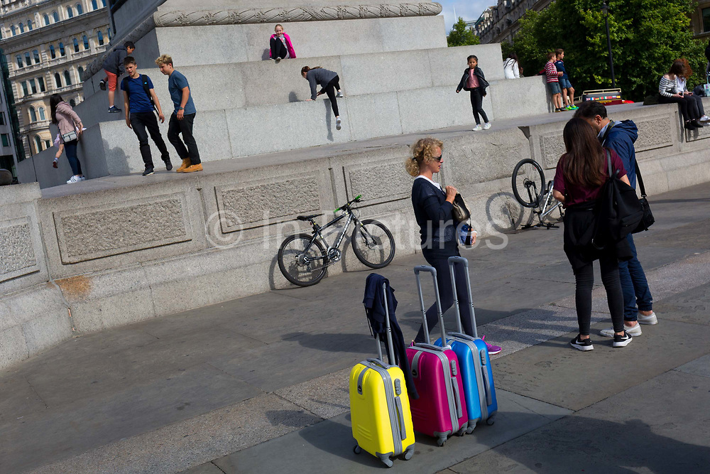 Coloured suitcases as young tourists play on the plinth of Nelsons Column in Trafalgar Square, on 10th August 2017, in London, England.