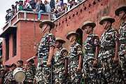 An former high ranking officer of the Nepalese army is cremated according to Hindu tradition in the Pashupatinath Temple complex. His regiment is paying their respects opposite the Bagmati River with many spectators following the lighting of the funeral pyre.