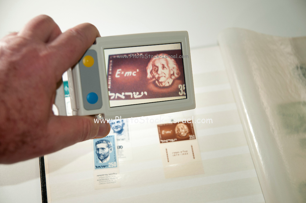 A vision impaired stamp collector uses a handheld electronic magnifier to inspect an Israeli 1956 Albert Einstein stamp in his stamp collection