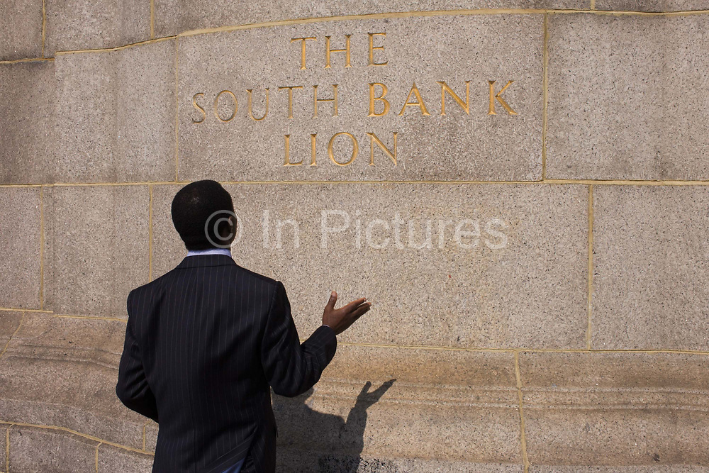 A religious man seemingly at prayer beneath the lion on the Southbank, south side of Westminster Bridge. With a hand outstretched during his private moment, the man is dressed in a dark pinstriped suit and stands still facing the wall with the lettering of the lion - an incongruous reason to pray to a stone animal, unseen above.