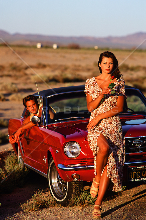 couple in the desert with a retro Mustang car