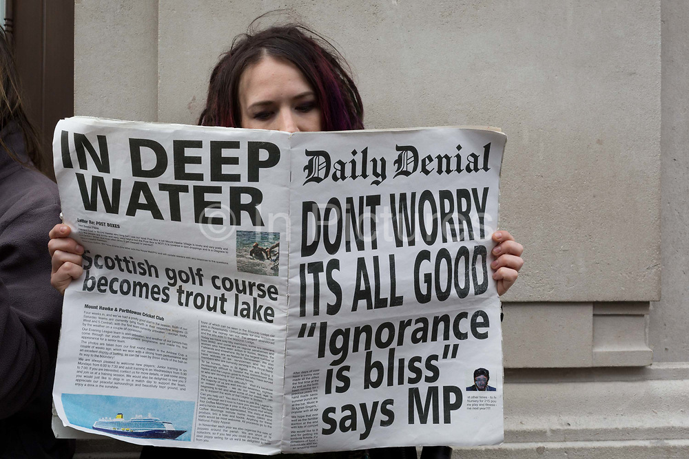 An environmental activist reads a copy of a fake newspaper with fictional headlines about the effects of global Climate Change during an occupation of Oxford Circus in central London, part of a two-week prolonged worldwide protest by members of Extinction Rebellion, on 18th October 2019, in London, England.