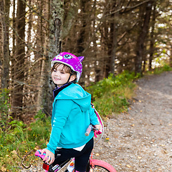 A young girl rides her bike at Quoddy Head State Park in Lubec, Maine.