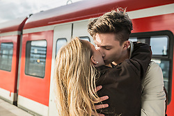 Young couple kissing at train station, Munich, Bavaria, Germany