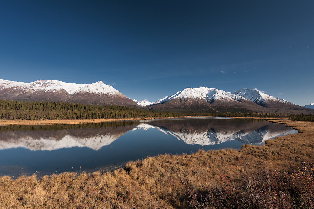 Mountains reflect in a small lake along the McCarthy Road in Alaska