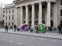 Ecocabs outside the historic GPO (General Post Office) on O'Connell Street in Dublin Ireland. Ecocabs are a fleet of environmentally friendly modern passenger tricycles operating a free shuttle service