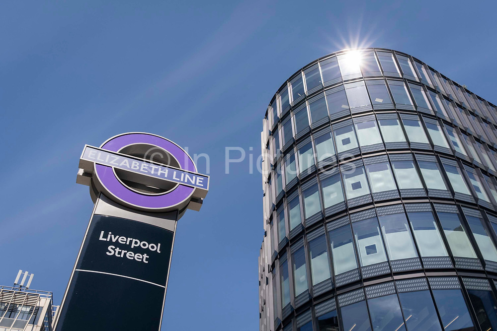 Nearby offices and Crossrails  Elizabeth Line logo at Liverpool Street in the City of London, the capitals financial district, on 8th June 2021, in London, England. Crossrail has been delayed again until 2022 and will need an extra £1.1bn to complete. Running through the heart of London, it will now open more than four years late and cost almost £4bn more than originally planned. The giant infrastructure scheme had originally planned to cost £14.8bn, with services planned to start operating in December 2018.