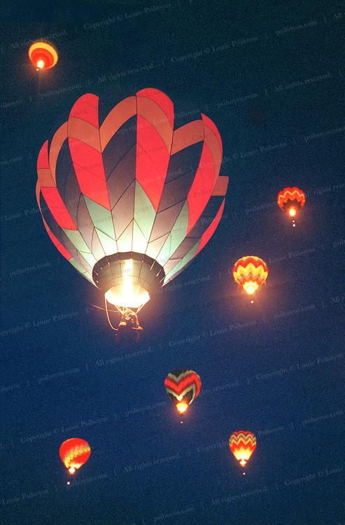 Balloons rise into the dawn at Coalinga, California ballooning festival.  Special jets of propane light up the interiors of the balloons to produce a dazzling effect.