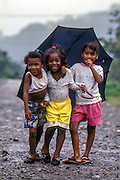 A trio of girls playing in the rain in Bahia Solano, El Choco