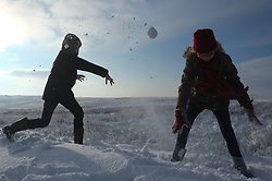© Licensed to London News Pictures. <br /> 27/12/2014. <br /> <br /> Castleton, United Kingdom.<br /> <br /> William Carter (L), 11 from Keldholme has a snowball fight with his sister Eleanor, 9 on the North Yorkshire Moors near Castleton after overnight snowfall caused disruption in some parts of the country.<br /> <br /> Photo credit : Ian Forsyth/LNP