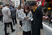 Chinese woman with eyes on her coat pockets texting on her phone during Chinese New Year celebrations in central London, United Kingdom. Tens of thousands of people gathered in the West End filling the streets and joining in with the festival atmosphere.