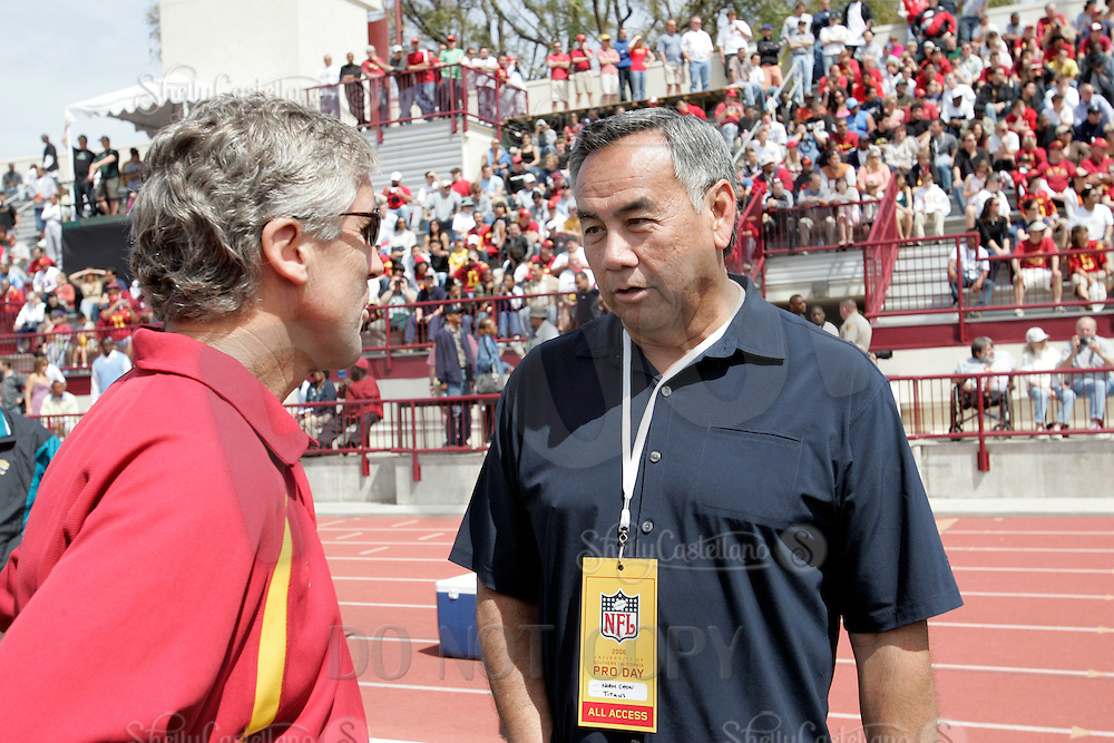 2 April 2006: College football coach Pete Carroll and former USC Trojans coach Norm Chow discuss players  at NFL pro-timing day at USC college campus in Los Angeles, CA.