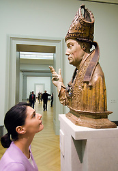 Visitor looking at wooden statue inside Bode Museum on Museuminsel in Berlin Germany 2009