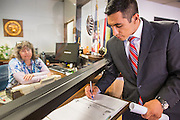 17 OCTOBER 2013 - PHOENIX, AZ:  JOSE BETO SOTO, field director of Citizens for a Better Arizona, signs the visitor log in the office of the Arizona Attorney General shortly before he was arrested during a protest in the offices of Arizona Attorney General. About 100 people came to the office of Arizona Attorney General Tom Horne to protest the decision by Horne to sue community colleges in Maricopa County that charge DREAM Act students who are residents of Arizona out of state tuition rather than in state resident tuition. Nearly 10 people were arrested in a planned civil disobedience during the protest.    PHOTO BY JACK KURTZ
