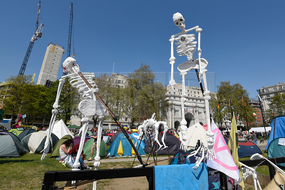 """© Licensed to London News Pictures. 22/04/2019. LONDON, UK. Fake skeletons made by activists gathered at Marble Arch during """"London: International Rebellion"""", on day eight of a protest organised by Extinction Rebellion.  Protesters are demanding that governments take action against climate change.  After police issued section 14 orders at the other protest sites of Oxford Circus, Waterloo Bridge and Parliament Square resulting in over 900 arrests, protesters have convened at the designated site of Marble Arch so that the protest can continue.  Photo credit: Stephen Chung/LNP"""