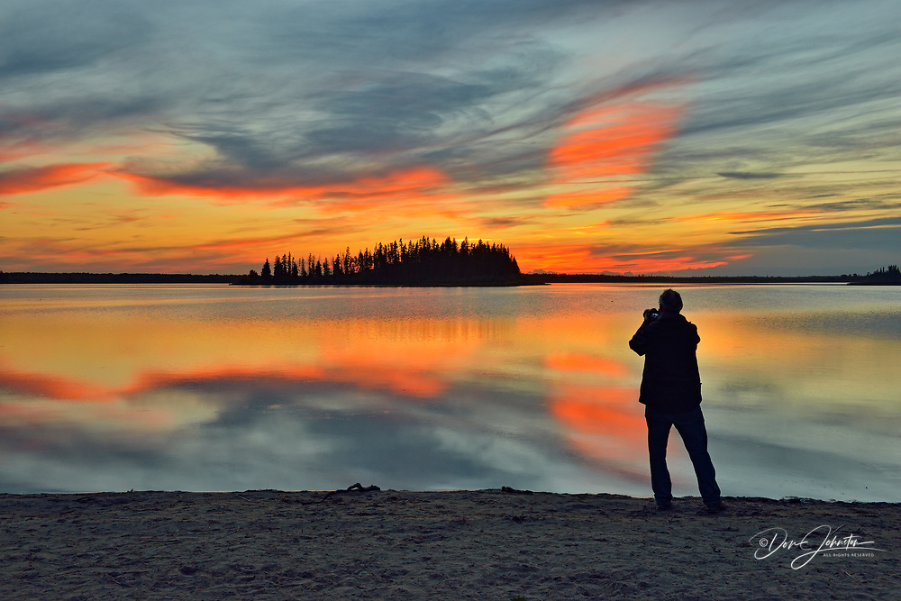 Photographer on Astotin Lake shoreline at sunset, Elk Island National Park, Alberta, Canada