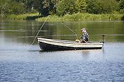 Fly fishing from a boat at Ringstead Lakes, Ringstead, Northampronshire.
