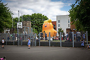 School children play basketball as the Trump Baby sitting team give the six metre high inflatable TrumpBaby his second London outing in Bingfield Park, Kings Cross , London, United Kingdom. 10th July 2018. He WILL fly above Parliament Square in Westminster when the real Trump, president of the United States arrives in the United Kingdom on the 13th of July 2018.