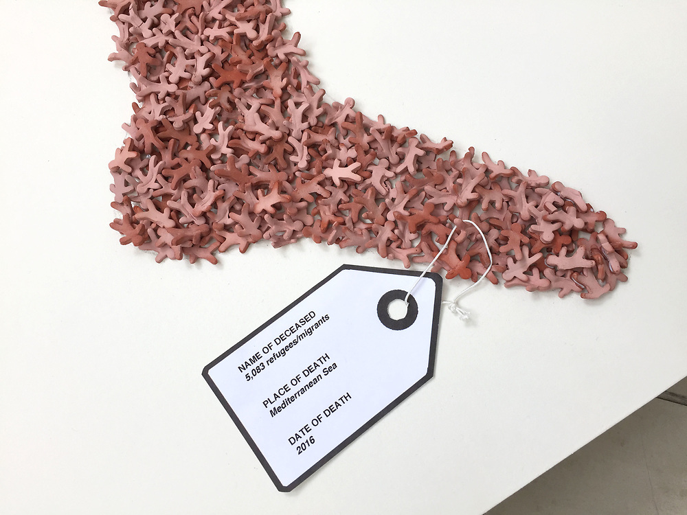 Sculpture. Detail of toe with identity tag.<br /> Dead in the water. 5,083 Gingerbread Refugees (2016).<br /> Data visualisation showing the number of refugees drowned in the Mediterranean sea in 2016 during the peak of the refugee crisis. Artwork made up of 5,083 tiny clay people.