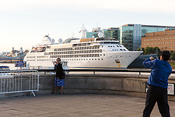 © Licensed to London News Pictures. 01/08/2017. LONDON, UK.  Tourists take a photograph in front of Silver Wind, a huge 514 feet long, 17,400 ton cruise liner seen moored next to HMS Belfast before she leaves London under Tower Bridge this morning after a brief visit, towed backwards by two tugs. Silver Wind carries just 296 passengers and its owner, Silversea claim that the ship has amongst the highest space-to-guest ratios in the cruise ship industry, with the largest suites measuring 1,314 square feet. Tickets cost thousands of pounds, but all guest expenses, even champagne are included in the price. Environmentalists claim the pollution created by giant cruise ships outweigh their economic benefits. The Port of London Authority (PLA) are conducting a work programme during 2017 to monitor air quality and pollution caused by river traffic on the River Thames.  Photo credit: Vickie Flores/LNP