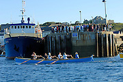 Isles of Scilly, 22 May 2009: Watched by spectators standing on the harbour wall, the gig Men A Uaur crosses the finish line during the Isles of Scilly Gig Association Men's Race from Nut Rock to St Mary's. Photo by Peter Horrell / http://peterhorrell.com