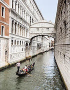 """The Bridge of Sighs (Ponte dei Sospiri, built 1602) spans the Roi di Palazzo and connects the Old Prison and interrogation rooms in the Doge's Palace to the New Prison located across the canal to the right, in Venice, Italy, Europe. The bridge can be seen from Ponte della Paglia next to the Doge's Palace. The bridge name, given by Lord Byron in the 19th century, comes from the suggestion that prisoners would sigh at their final view of beautiful Venice through the window before being taken down to their cells. In reality, the days of inquisitions and summary executions were over by the time the bridge was built and the cells under the palace roof were occupied mostly by small-time criminals. Little could be seen from inside the Bridge due to the stone grills covering the windows. A local legend says that lovers will be granted eternal love and bliss if they kiss on a gondola at sunset under the Bridge of Sighs as the bells of St Mark's Campanile toll. This legend served as a plot line for the movie """"A Little Romance,"""" featuring Laurence Olivier and Diane Lane. Venice (Venezia), founded in the 400s AD, is capital of Italy's Veneto region, named for the ancient Veneti people from the 900s BC. The romantic City of Canals stretches across 100+ small islands in the marshy Venetian Lagoon along the Adriatic Sea, between the mouths of the Po and Piave Rivers. The Republic of Venice was a major maritime power during the Middle Ages and Renaissance, a staging area for the Crusades, and a major center of art and commerce (silk, grain and spice trade) from the 1200s to 1600s. The wealthy legacy of Venice stands today in a rich architecture combining Gothic, Byzantine, and Arab styles. Venice and the Venetian Lagoon are honored on UNESCO's World Heritage List."""