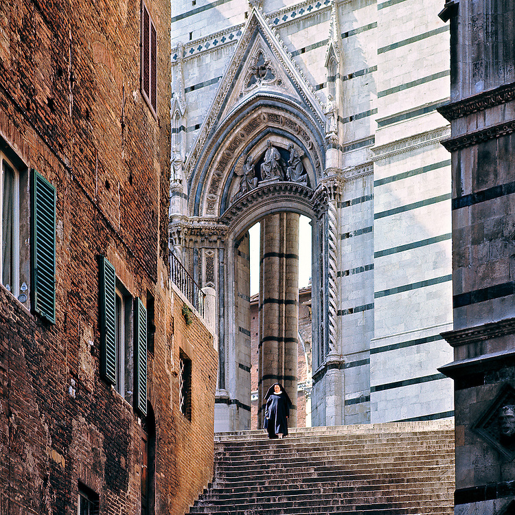 A robed nun descends the stone stairs of a cathedral in Siena, Tuscany, Italy.