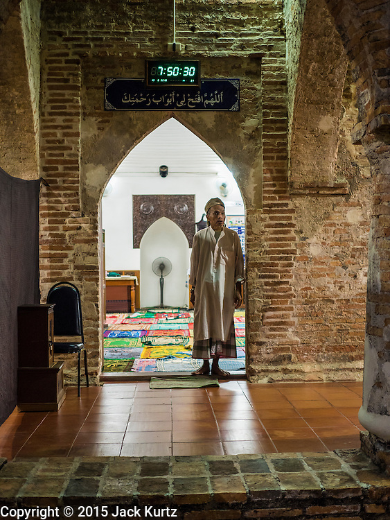 19 JUNE 2015 - PATTANI, PATTANI, THAILAND: A man stands in the mosque doorway during Ramadan services at Krue Se Mosque. Krue Se Mosque was started in 1583 but never completely finished. Ramadan is the ninth month of the Islamic calendar, and is observed by Muslims worldwide as a month of fasting to commemorate the first revelation of the Quran to Muhammad according to Islamic belief. This annual observance is regarded as one of the Five Pillars of Islam. Islam is the second largest religion in Thailand. Pattani, along with Narathiwat and Yala provinces, all on the Malaysian border, have a Muslim majority.             PHOTO BY JACK KURTZ