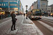 Een meisje wacht op de stadsbus die voorbij komt rijden door de sneeuw