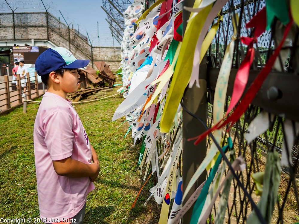 09 JUNE 2018 - IMJINGAK, PAJU, SOUTH KOREA: A South Korean boy looks at prayer flags hanging on a fence near the northernmost point on the South Korean side of the Korean DMZ in Imjingak. Imjingak is a park and greenspace in South Korea that is farthest north most people can go without military authorization. The park is on the south bank of Imjin River, which separates South Korea from North Korea and is close the industrial park in Kaesong, North Korea that South and North Korea have jointly operated.     PHOTO BY JACK KURTZ