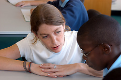 Teaching assistant talking to pupil in primary school; West Yorkshire UK